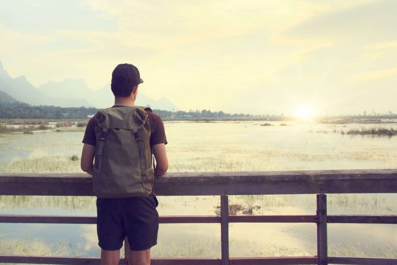 Junge mit Rucksack steht auf einer Brücke und schaut auf einen See