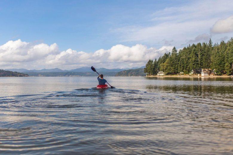 Mensch fährt mit Kanu auf den See hinaus