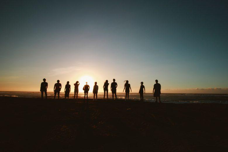Eine Gruppe Menschen steht in der Dunkelheit und betrachtet den Sonnenuntergang
