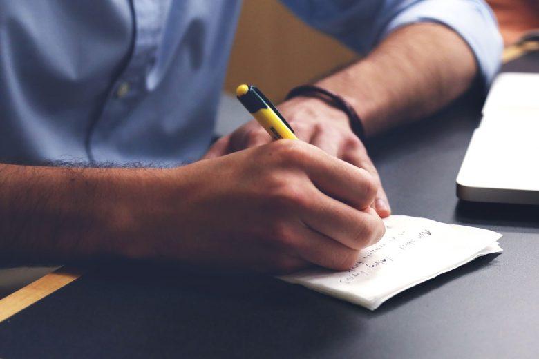 Mann notiert sich etwas in Notizbuch
