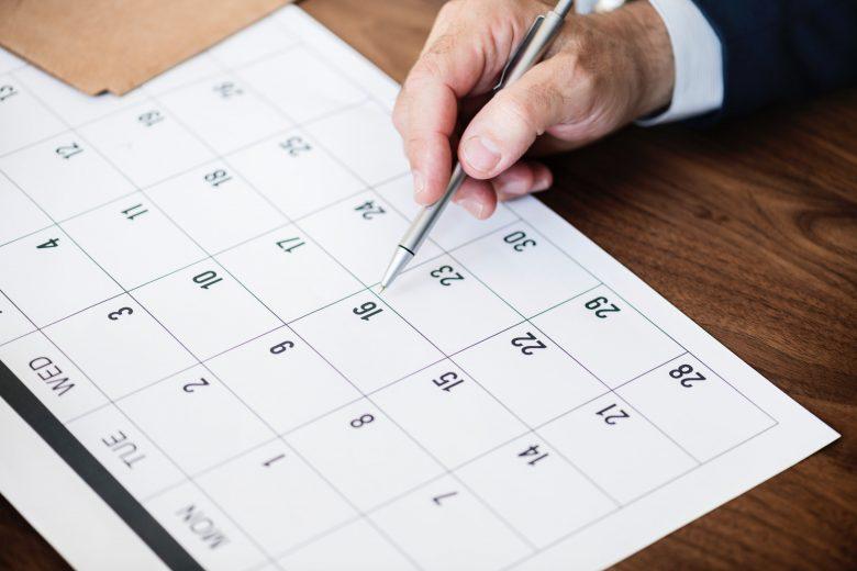 Hand zeigt auf einen möglichen Termin im Kalender
