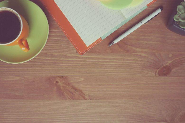 Kaffee, ein Notizbuch und ein Kaktus
