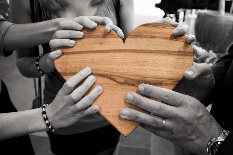 Hände halten ein Herz aus Holz