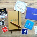 Auf dem Tisch liegen Werbeartikel verschiedener Social-Media-Kanäle