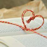 Herz aus einer Kordel liegt auf einem Buch