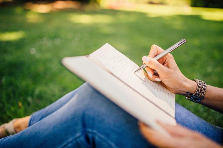 Person sitzt im Gras und schreibt in ein Notizbuch